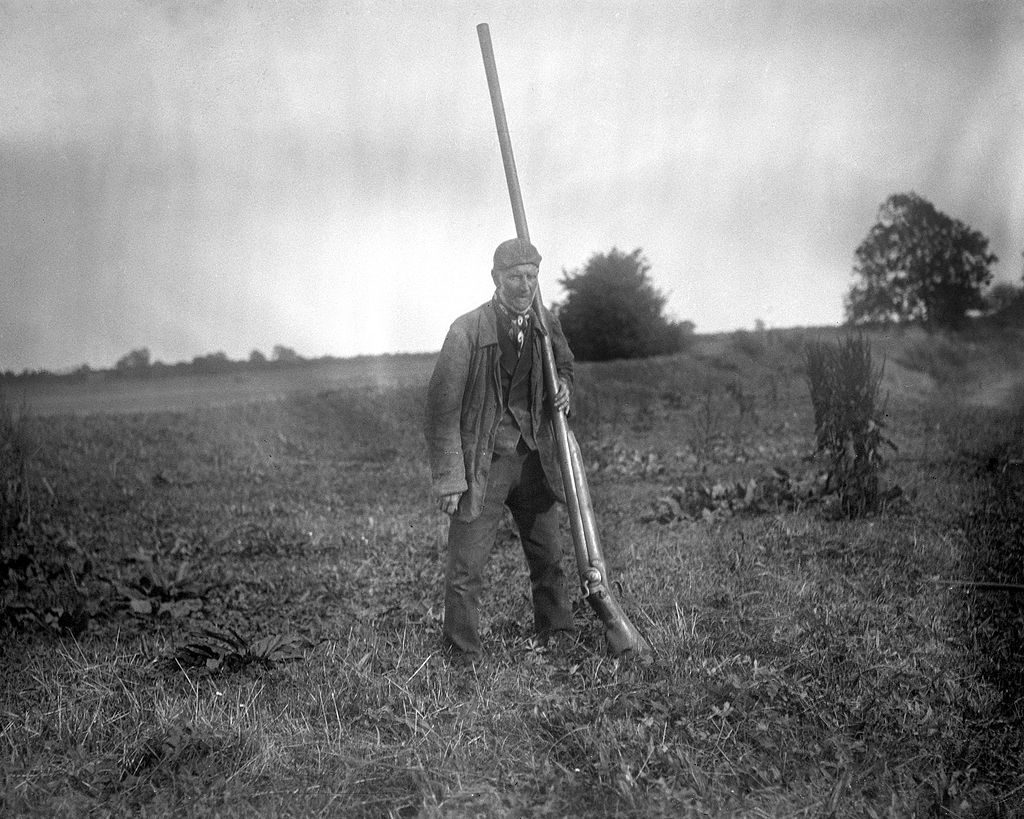 A man standing with a 2 gauge shotgun, aka a punt gun.